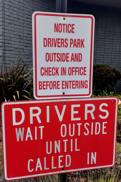 "photo of signs: ""Notice: Drivers Park Outside and Check in Office Before Entering"" and ""Drivers: Wait Outside Until Called In"""