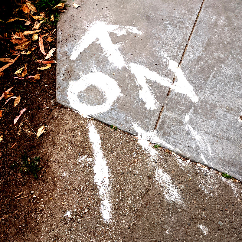 photo: chalk marks on ground: phrase 'on in' with an arrow