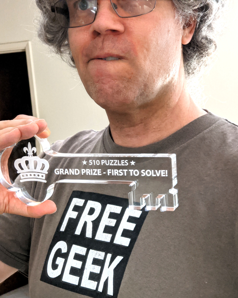 [picture: Selfie posing with nifty key etched with '★ 510 Puzzles ★ Grand Prize - First to Solve!']