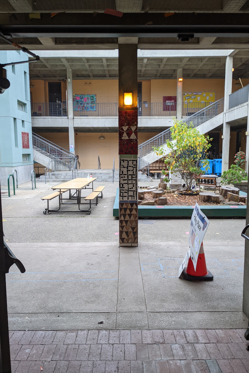 Courtyard at Grattan Elementary with tile-mural pillar decoration and a polling place sign