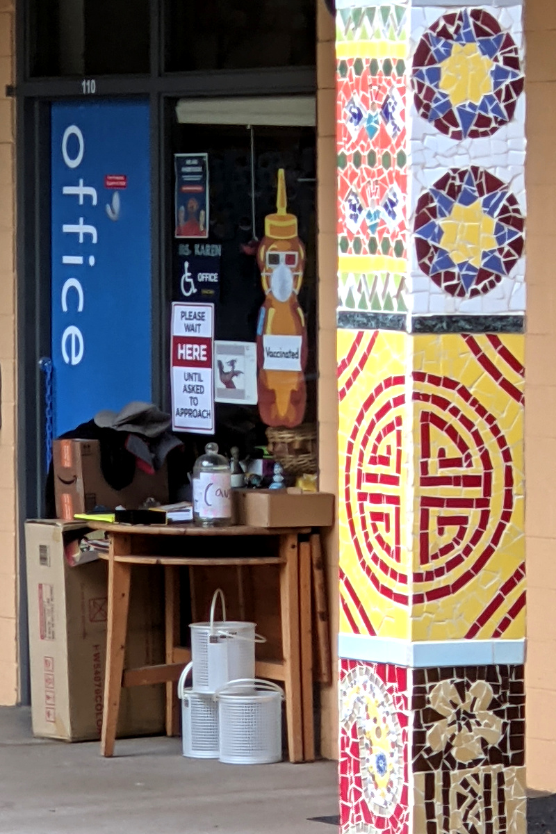 Office door at Grattan Elementary with tile-mural pillar decoration and Fnnch honeybear art